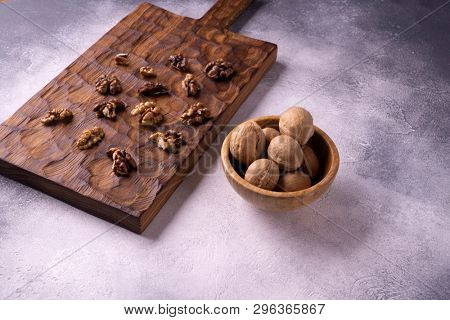 Walnuts in wooden bowl and on wooden carved board on bright textured surface, side view. Healthy nuts and seeds composition.