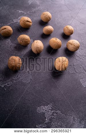 Bunch of whole walnuts on dark blue slate surface. Healthy diet composition, background