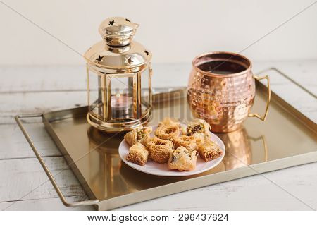 Assorted Baklava, Coffee In A Brass Mug And Lantern With Burning Candle Served On A Gold Colored Met