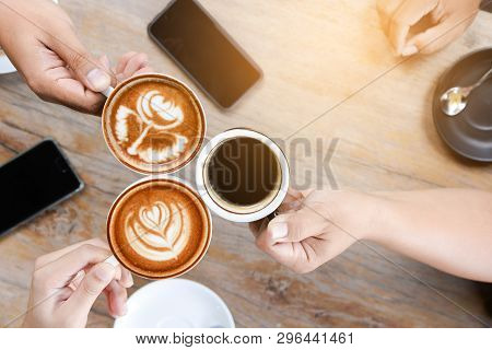 Group Of People Having A Meeting After Successful Business Negotiation In A Coffee Shop.drinking Hot