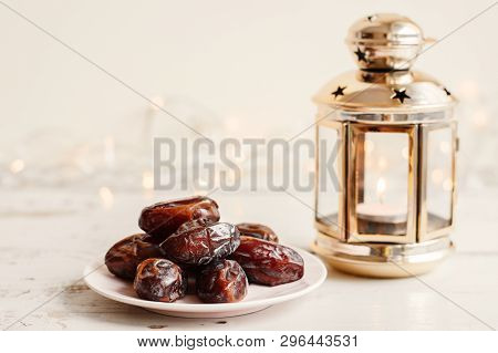 Dried Dates On White Plate And Lantern With Burning Candle On White Wooden Table, Bokeh Light On Bac