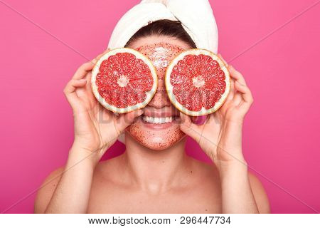 Close Up Portrait Of Positive Attractive Girl Smiling Sincerely, Holding Two Parts Of Grapefruit, Co
