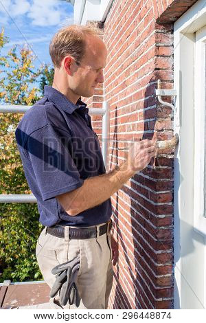 Caucasian Male Painter Painting White Window Frame In Frontage Of House With Brush