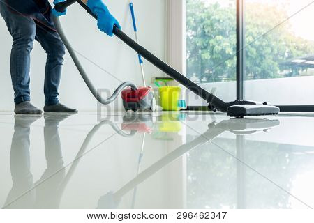 Young Attractive Man Is Cleaning Vacuum Commercial Cleaning Equipment On Floor At Home Helping Wife