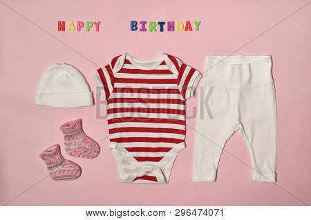 Set Of Clothes For The Newborn. Colored Inscription Happy Birthday On A Pink Background.