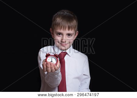 Smiling Schoolboy With A Red Alarm Clock In His Hands. Morning Concept. Black Background