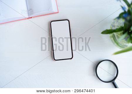 Smartphone With White Blank Screen. Notebook, Magnifier And Flowers On Table
