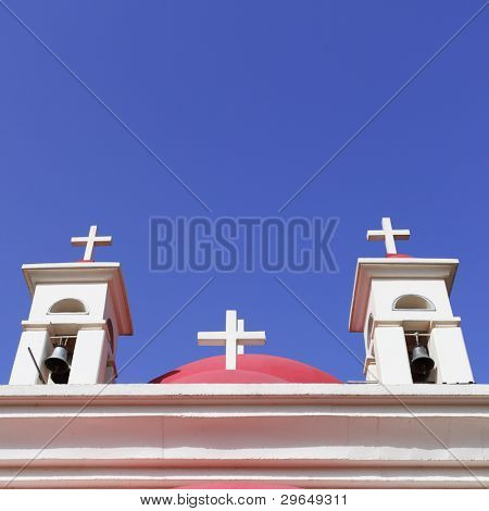 Roof of temple with crosses against blue sky