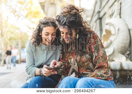 Two Friend Girls Using Cellphone Outdoors.