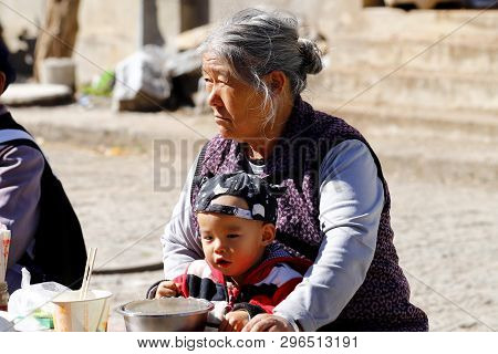 Shigu, Yunnan, China - November, 2018. An Old Chinese Woman With A Small Child On The Road In The Vi