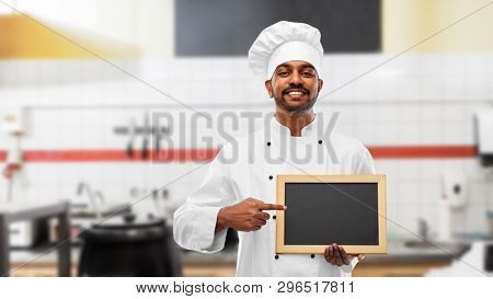 cooking, profession and people concept - happy male indian chef in toque with blank chalkboard for menu over restaurant kitchen background