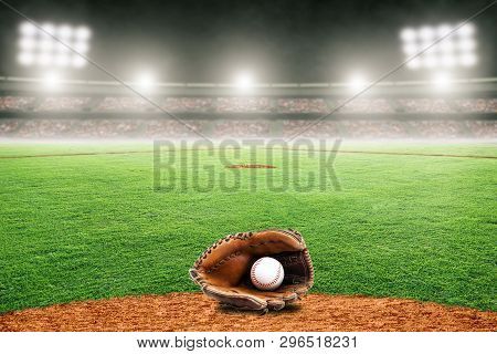 Baseball Glove On Field At Brightly Lit Outdoor Stadium. Focus On Foreground And Shallow Depth Of Fi