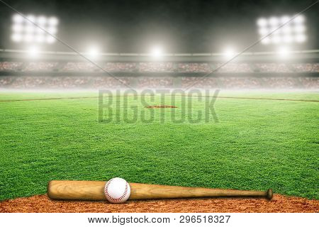 Baseball Bat And Ball On Field At Brightly Lit Outdoor Stadium. Focus On Foreground And Shallow Dept