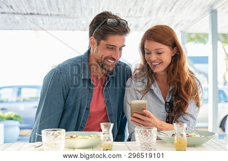 Young happy couple using mobile phone sitting at restaurant. Smiling man pretty woman looking at smartphone while enjoying lunch on terrace cafe. Portrait of mature couple using cellphone at the sea.