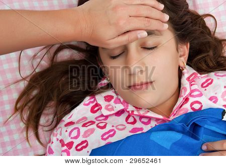 Hispanic girl sick with fever while a woman's hand touches her forehead