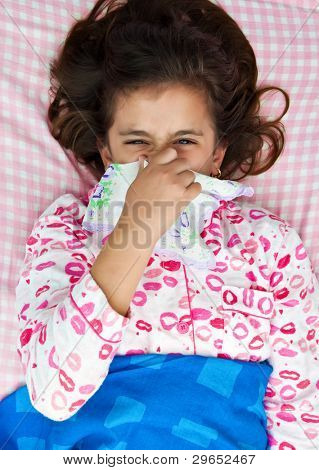 Hispanic girl blowing her nose and laying in her bed wearink pink pajamas
