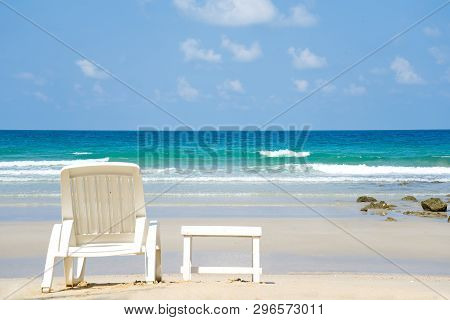 Seascape View Of Beach Facing Out To The Ocean. White Beach Chair And Small Table Put On The Beach.
