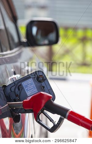 Fill The Car With Fuel. The Car Is Filled With Gasoline At A Gas Station. Gas Station Pump. Man Refu