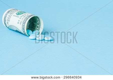Money Dollar Rolled Up With Pills Flowing Out Isolated On Blue Background, High Costs Of Expensive M