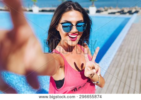 Close-up Selfie-portrait Of Attractive Brunette Girl With Long Hair Standing Near Pool. She Wears Pi