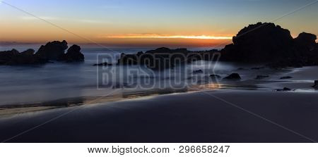 poster of A long exposure sunrise over the surf on flynns beach at port maquarie on the new south wales mid coast. golden sunshine lights up the sky and the waves look soft and fluffy due to the long exposure