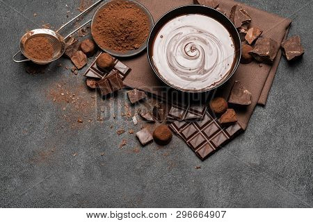Ceramic Bowl Of Chocolate Cream Or Melted Chocolate And Pieces Of Chocolate Isolated On Dark Concret
