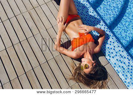 Attractive Blonde Girl With Long Hair Is Lying On Flor Near Pool. She Wears Orange Bikini, Sunglasse