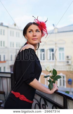 Beautiful young woman wearing black evening dress holding white rose on balcony outdoor