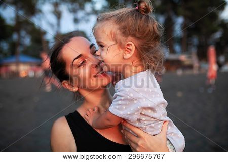 Happy Mother And Her Little Daughter Outdoor. Mom And Daughter Enjoying Nature Together On The Black