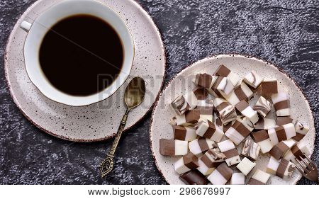 Cup Of Coffee And Delicious Jelly Dessert With White & Brown Layers On A Spotty Plate. Dessert Spoon