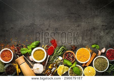 Set Of Various Spices And Herbs On Black Slate Background. Pepper, Turmelic, Ginger, Saffron, Basil,