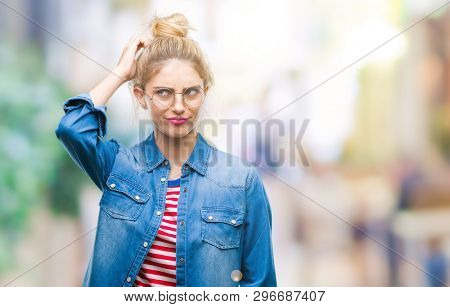 Young beautiful blonde woman wearing glasses over isolated background confuse and wonder about question. Uncertain with doubt, thinking with hand on head. Pensive concept.