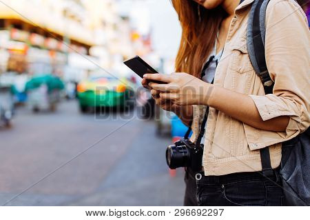 Young Asian Female Tourist Woman Using A Mobile Phone In Bangkok, Thailand. Calling A Cab Or Finding