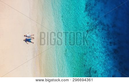Aerial View Of A People Couple On The Beach On Bali, Indonesia. Vacation And Adventure. Beach And Tu