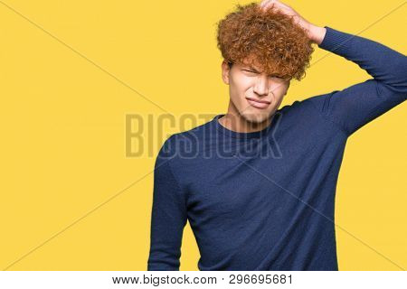Young handsome man with afro hair confuse and wonder about question. Uncertain with doubt, thinking with hand on head. Pensive concept.