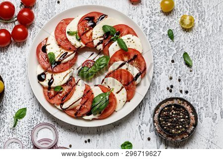 Italian Caprese Salad With Ripe Tomatoes, Fresh Basil And Mozzarella Cheese On Grey Stone Background