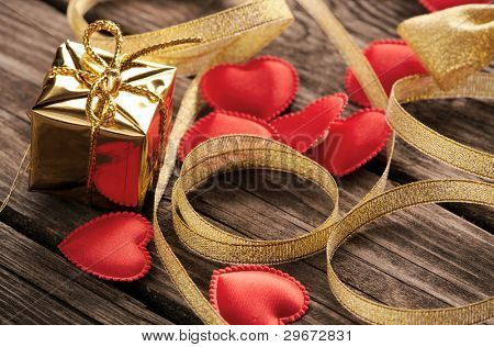 Small hearts with gold curved ribbon and small gold gift box on old wood.
