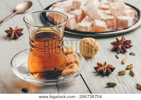 Tea in arab glass with turkish delight Rahat Lokum and different spices over wooden surface poster