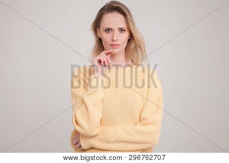 Young Blonde Woman With Peaceful Face Expression Standing Against Grey Background Keeping Her Finger