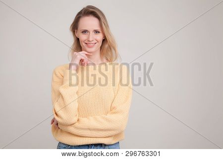 Young Blonde Woman With Peaceful Face Expression Standing Against Grey Background, Smiling And Keepi