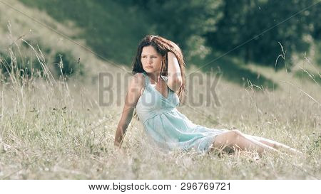 brooding young woman sitting on the grass of a summer meadow. poster