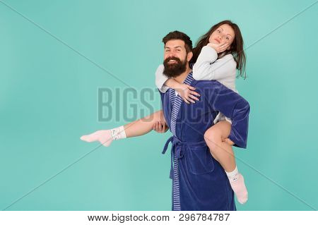 Close Relationship. Handsome Young Man Giving His Girlfriend Piggyback Ride. Couple In Bathrobes Hav