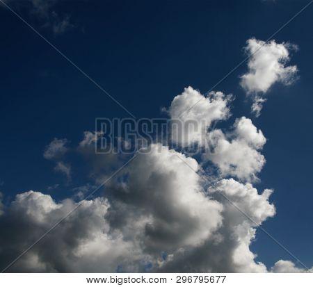 A Spectacular Vibrant Sky Cloudscape Scene, With White Coloured Billowing Cumulonimbus Cloud Formati