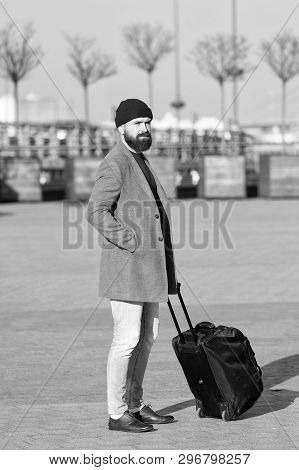 poster of Man bearded hipster travel with big luggage bag on wheels. Let travel begin. Traveler with suitcase waiting transportation to airport railway station. Ready to travel. Carry travel bag. Business trip.