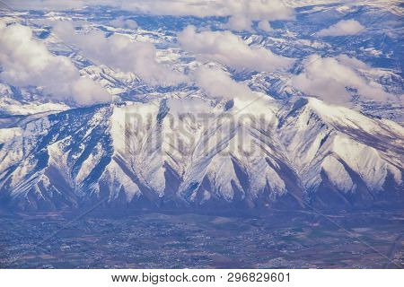 Aerial View From Airplane Of The Wasatch Front Rocky Mountain Range With Snow Capped Peaks In Winter