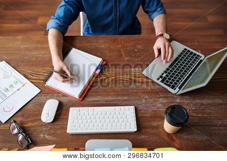Overview of young contemporary manager or employee making notes in notebook while browsing in the net and analyzing online data