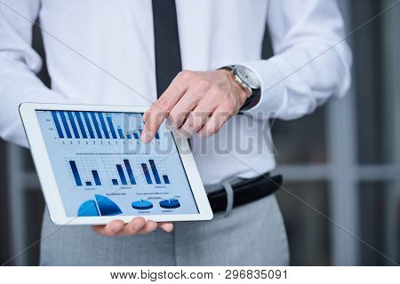 Hand of young elegant economist or analyst in formalwear pointing at financial chart in tablet while making presentation