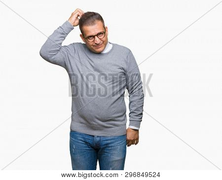 Middle age bussines arab man wearing glasses over isolated background confuse and wonder about question. Uncertain with doubt, thinking with hand on head. Pensive concept.