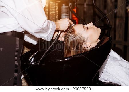 Gorgeous Cute Young Woman Enjoying Head Massage While Professional Hairdresser Applying Shampoo Her