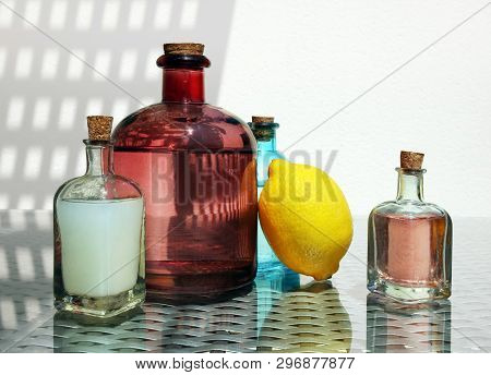 Still Life With Cold Fresh Lemonade, Compote And Lemon Juice In The Small Vintage Glass Botlles Agai
